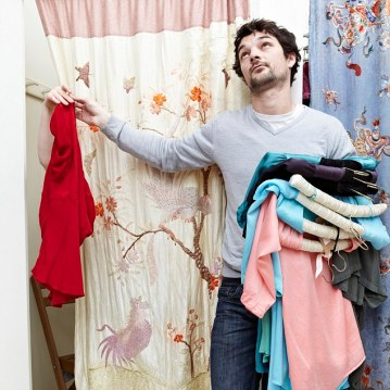 Man holding clothes by a changing room